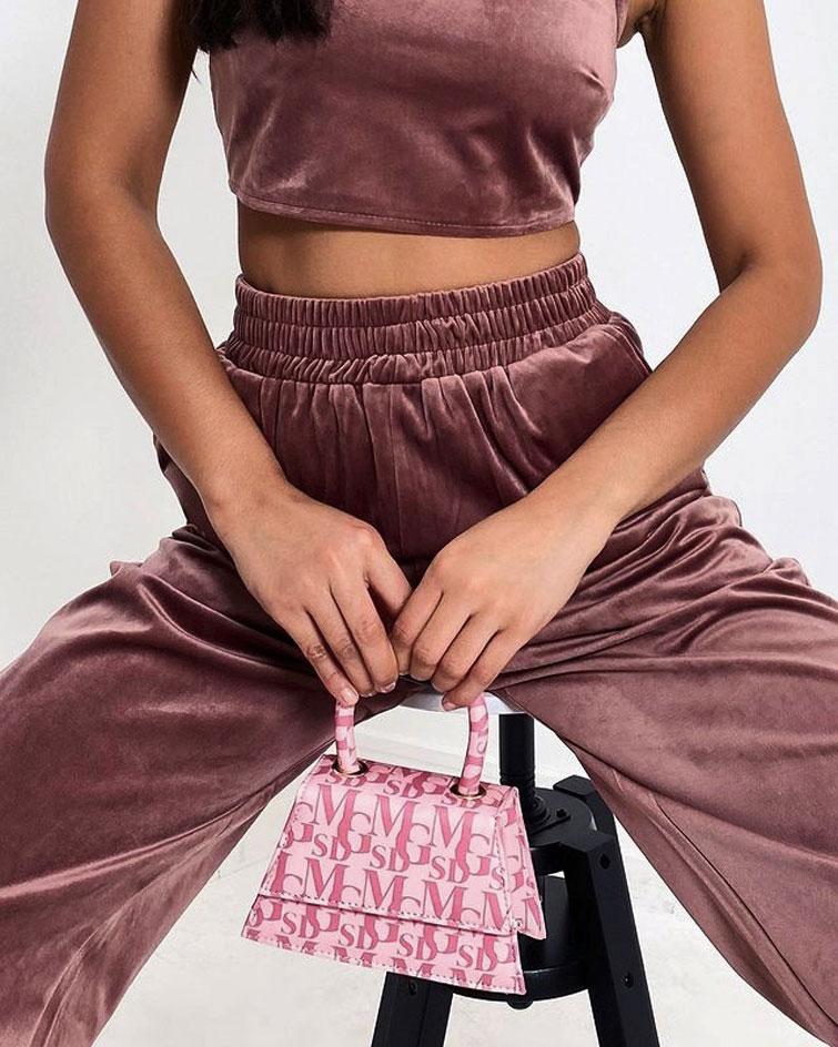 Eine Frau trägt ein rosa Samt-Ensemble mit trendiger Handtasche