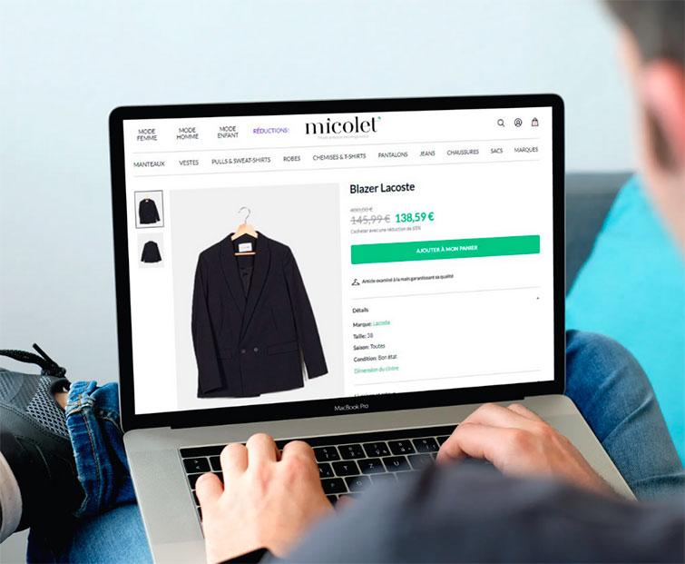 photo d'un homme consultant un article sur un ordinateur sur Micolet qui propose la vente et l'achat de vêtements d'occasion pour hommes, femmes et enfants