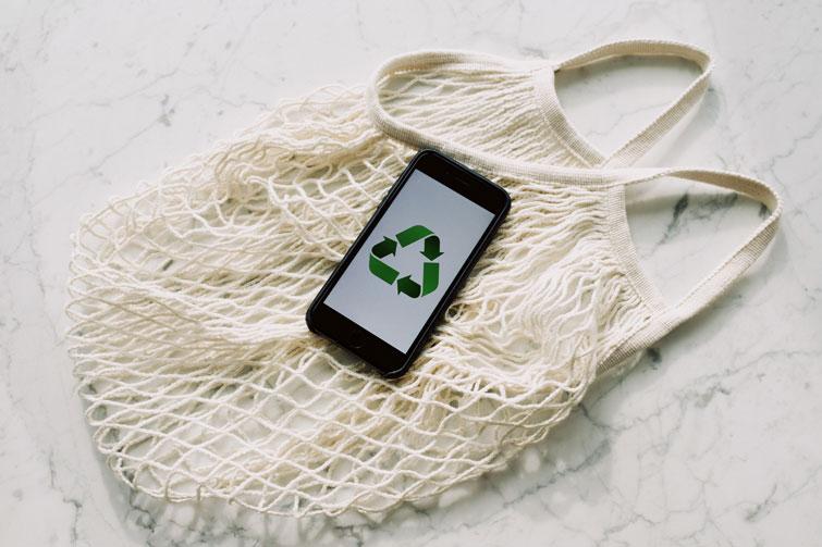Sac et téléphone portable signifiant le recyclage de vêtements contre bon d'achat