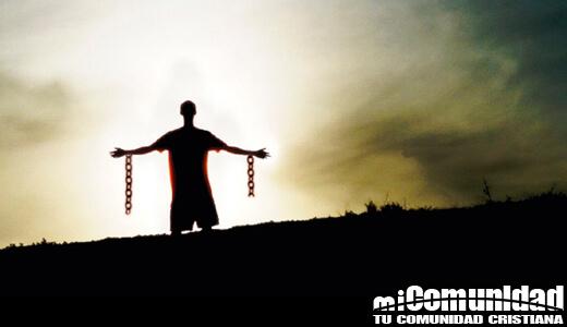 En la imagen en el horizonte un hombre con los brazos abiertos con cadenas rotas
