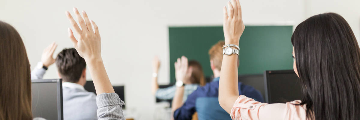 Don't deprive yourself of the value of formal training. Hear, a group of professionals seated in front of computers raise hands in a classroom training session.