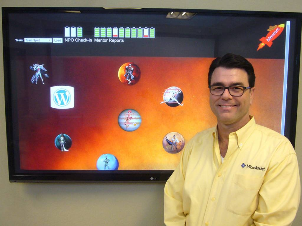 "Microassist CTO Hiram Kuykendall with accessibility training game screen displayed behind him. Game shows superhero characters on planets with a rocket labeled ""Mentors."" Battery icons and a WordPress logo are also on the screen."