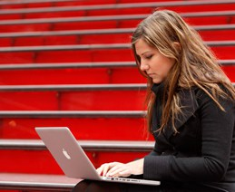 College student sitting in bleachers with Apple Macbook.
