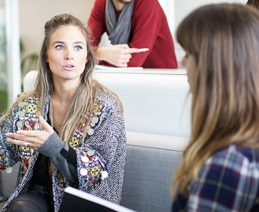 Two women in discussion during work meeting.