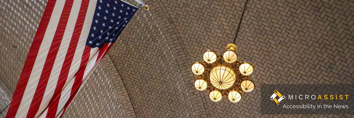 American flag and lights hang from ceiling at Ellis Island building. Microassist Accessibility in the News
