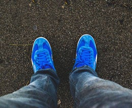 Personal closeup perspective of person looking down at blue tennis shoes on pavement.