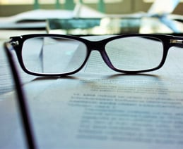 Reading glasses on stack of papers.