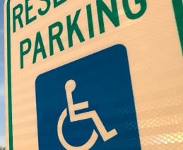 "cropped ""reserved parking"" sign with wheelchair symbol"