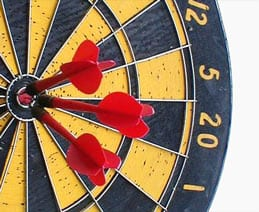 A target with three darts at the bullseye.
