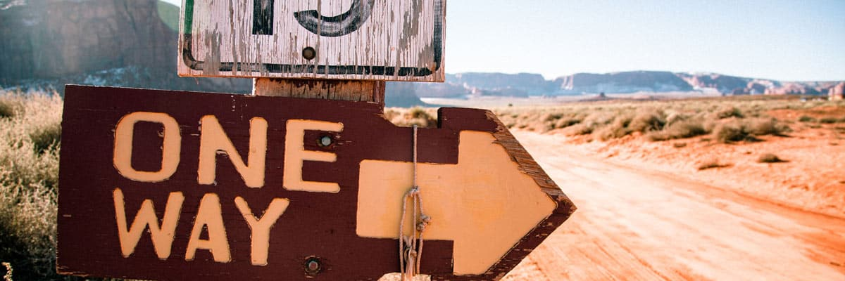 "Worn road sign in a dry, barren desert says ""One Way"" with arrow."