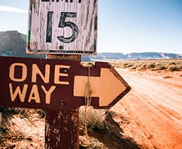 "road sign barren desert says ""One Way"" with arrow."