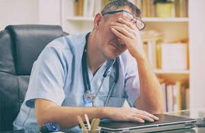 A provider showing signs of physician burnout with visible signs of exasperation