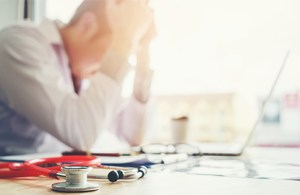 Physician frustrated with HIT Adoption in front of a computer