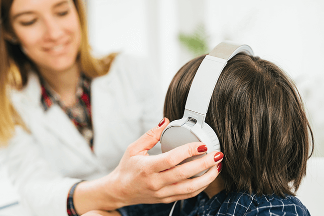 Doctor adjusts headset for patient's hearing exam