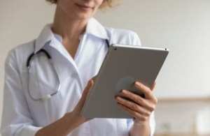 A female doctor holds a tablet in a blurred out doctors office.