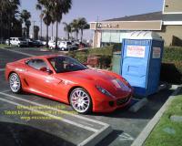 Ferrari parked next to a portable toilet