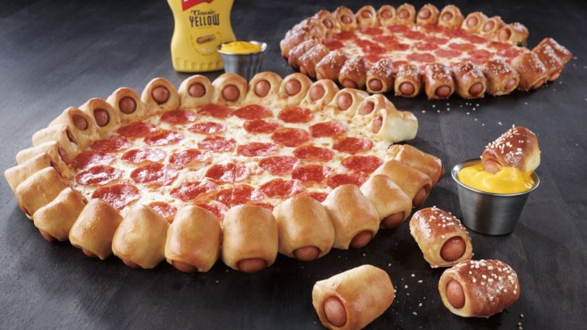 Two pizza hut hot dog pizzas. One with pretzel dogs, the other regular. Both have pepporoni