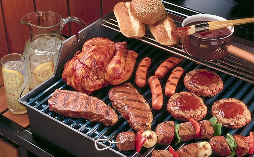Grill with meats on it grilling (hot dogs, steak, turkey, kabobs, hamburger buns)