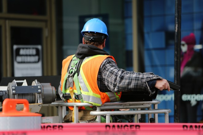 construction worker with blue hard hat and orange safety vest