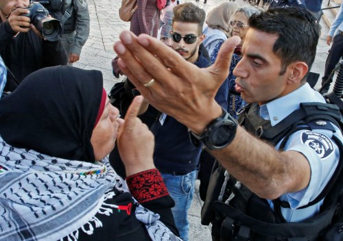 A Palestinian woman argues with a member of the Israeli security forces as they disperse a demonstration outside the Damascus Gate in the old city of Jerusalem on 15 May, 2018 marking the 70th anniversary of Nakba (AFP)