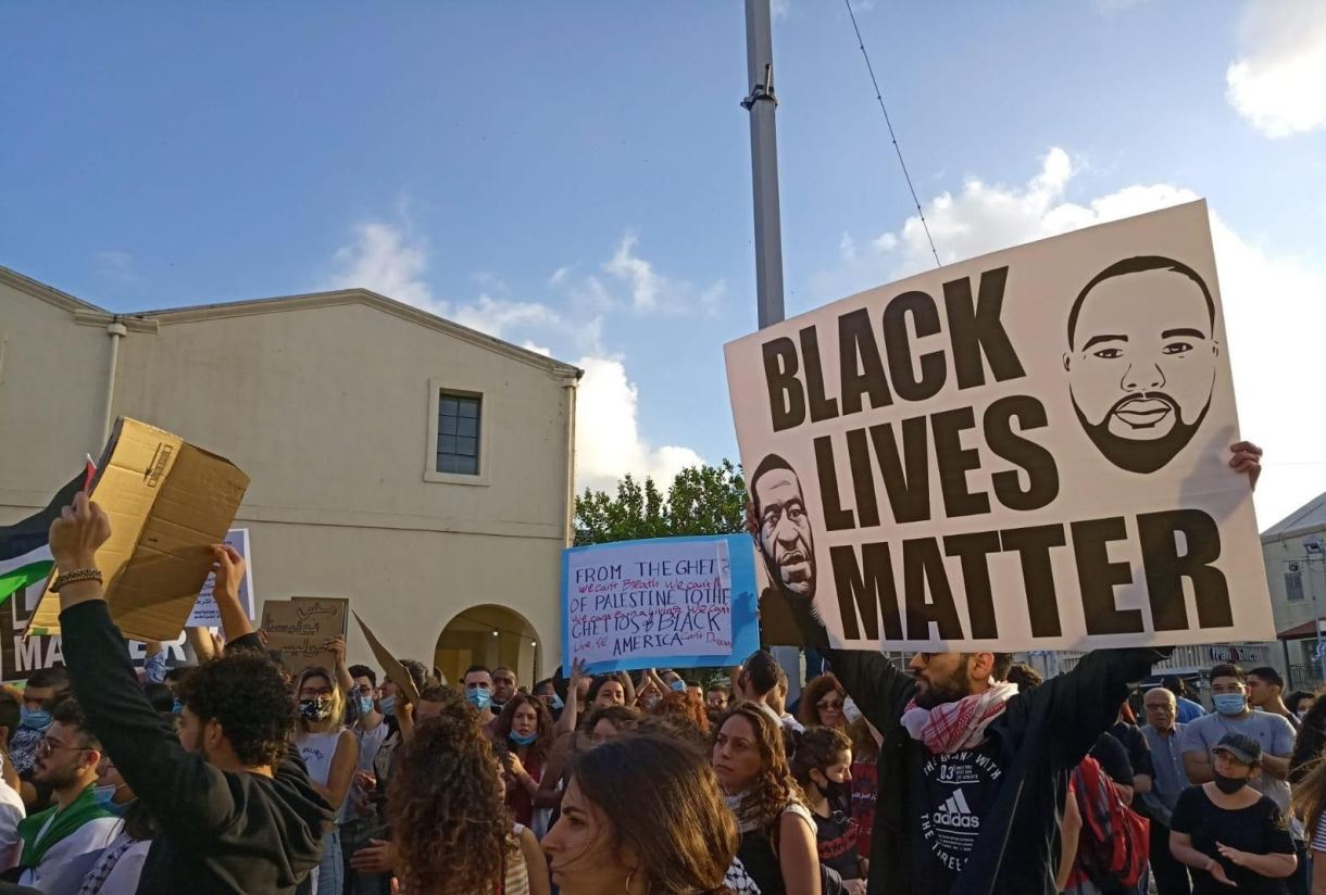 A demonstrator holds up a Black Lives matter protester in Haifa on 2 June (MEE)