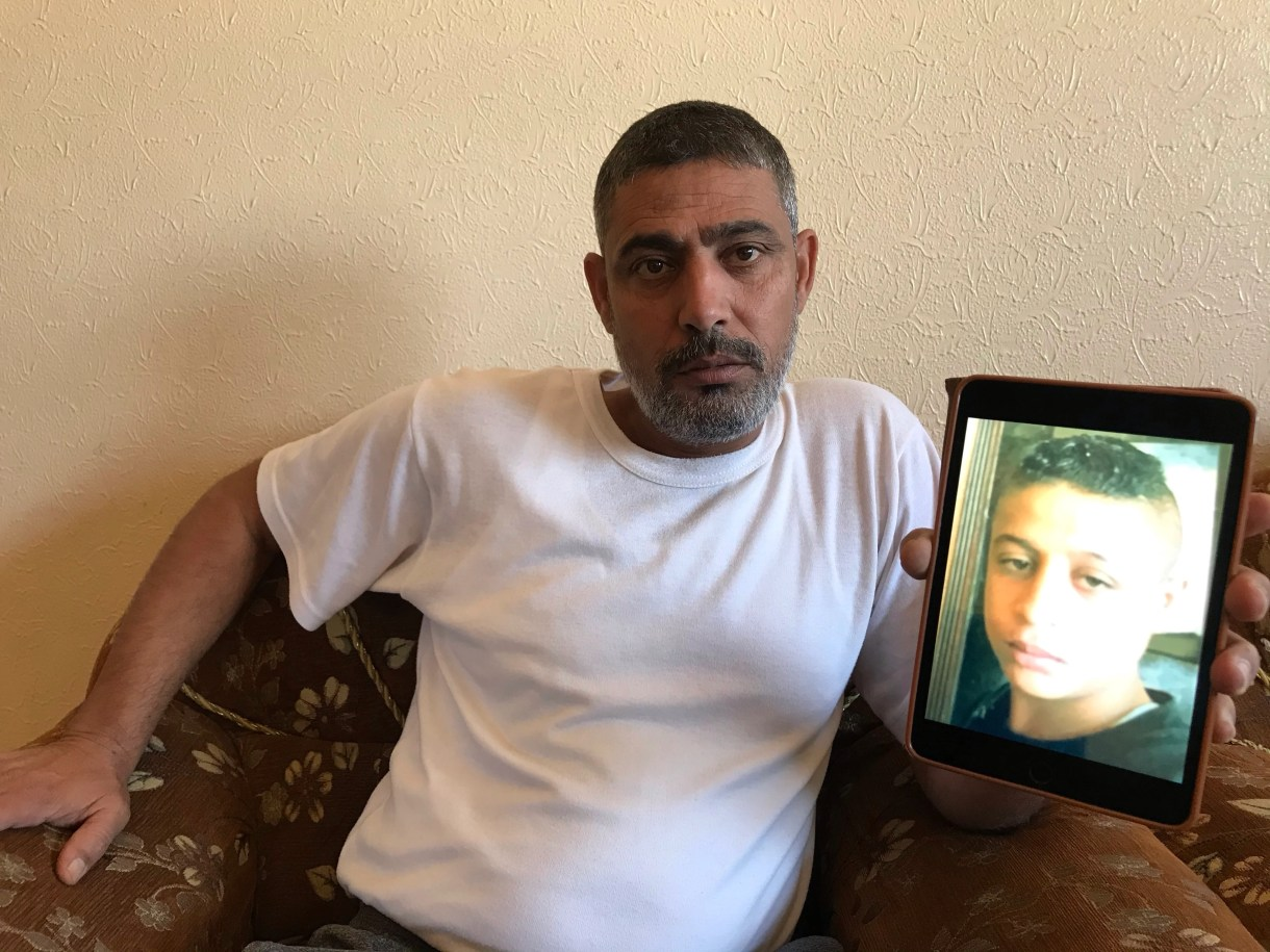 Othman Hilles' father Rami holds a picture of his dead son (MEE/Moatasim Dalloul)