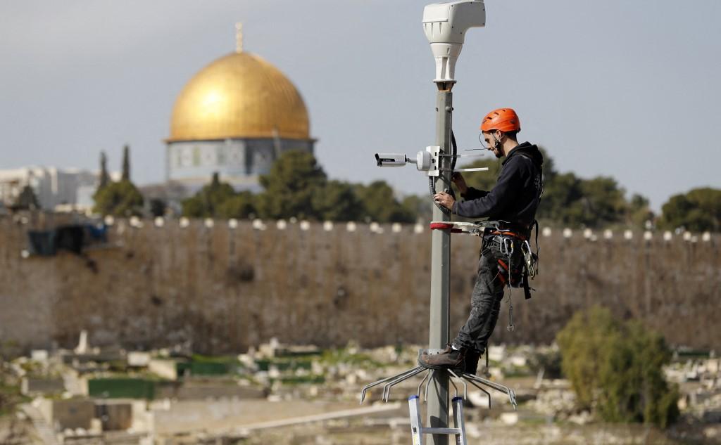 An Israeli technician installs a surveillance camera in occupied East Jerusalem in 2019 (AFP)