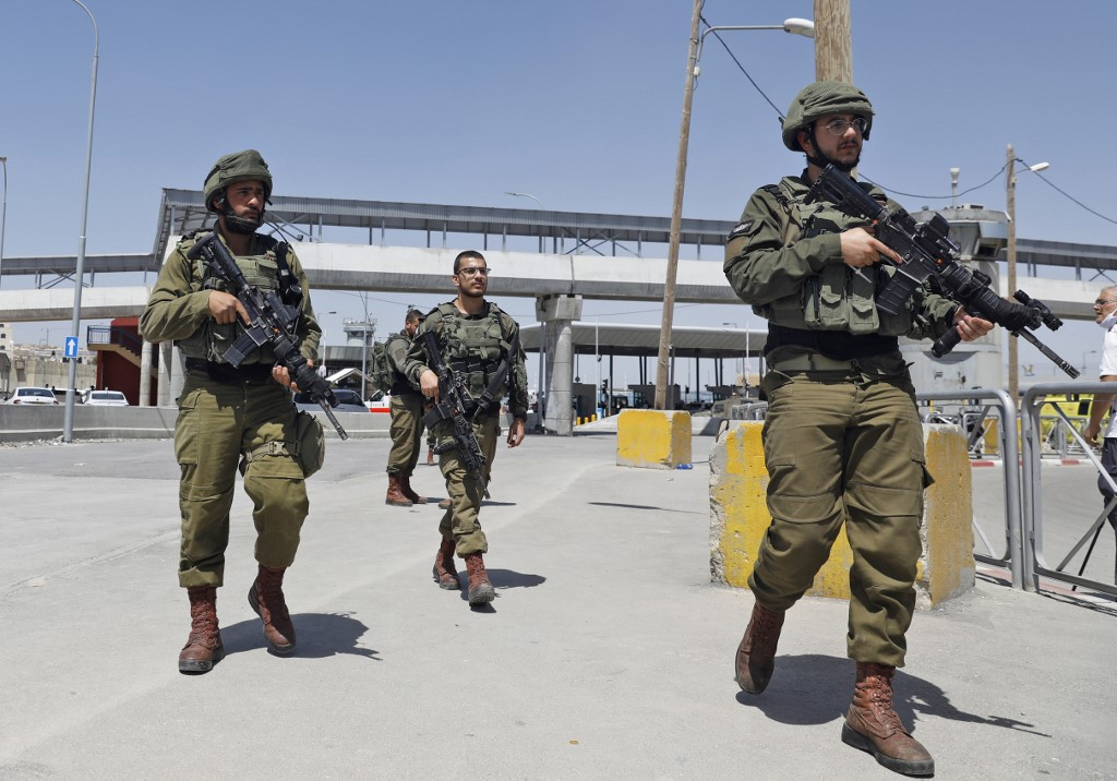 Israeli soldiers gather at Qalandiya checkpoint in the occupied West Bank on 12 May (AFP)