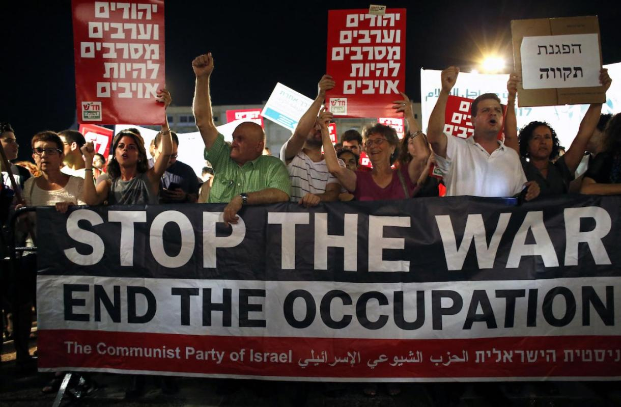 """Israeli Communist Party supporters hold a """"stop the war"""" banner as thousands of them gather at the Rabin Square in Tel Aviv on 62 July 2014 (AFP)"""