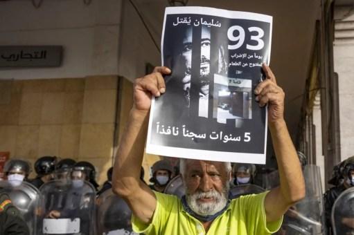 Un militant marocain tient une affiche avec la photo du journaliste marocain Souleimane Raissouni, condamné à cinq ans de prison pour « agression sexuelle », le 10 juillet 2021 à Rabat (AFP/Fadel Senna)