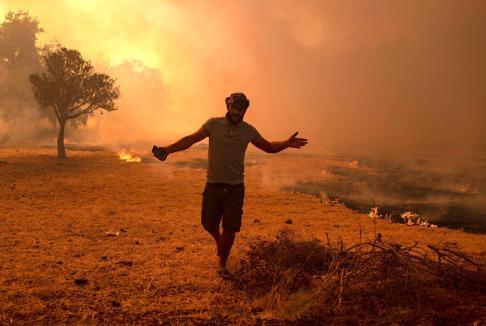 Un homme fuit devant le feu qui avance, dans la région de Marmaris, le 2 août 2021 (AFP/Yasin Akgül)