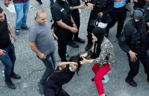 Une manifestante tombe à terre lors d'une échauffourée avec un policier palestinien au cours d'une manifestation en réaction à la mort de Nizar Banat, le 26juin2021 à Ramallah, en Cisjordanie occupée(Reuters)