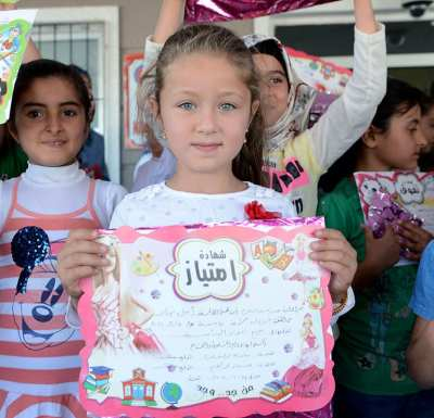 KILIS, TURKEY: Syrian students living in refugee camps in Turkey receive their end of year school certificates