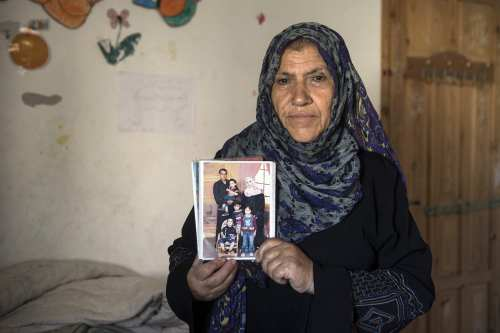 Khadija Kilani holds the photo of her brother Ibrahim Kilani, his wife Taghreed and their 4 children, Beit Lahiya, September 18, 2014 [Anne Paq/Activestills.org]