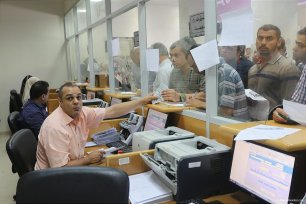 Image of Palestinian workers waiting in line to receive their pay check at the post office [Apaimages]