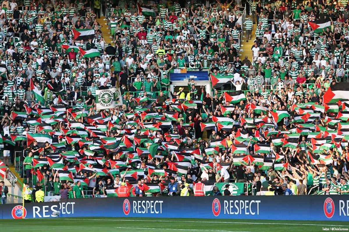 Fans of Scotland's Glasgow Celtic FC display Palestinian flags while playing against Israel's Hapoel Beer Sheva FC [Image credit: Twitter / @ChrisGunness]