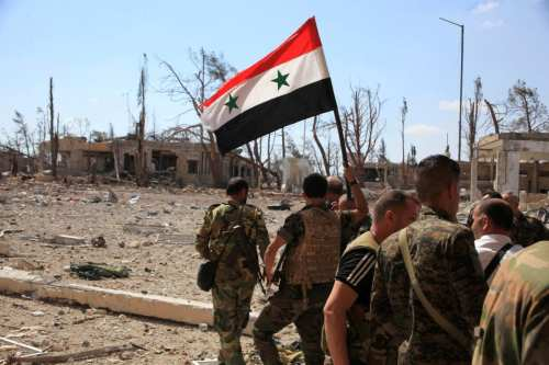 Syrian President Bashar Al-Assad's military forces walk past a military complex with a Syrian national flag in Syria on September 5 2016 [SANA/Handout via REUTERS]