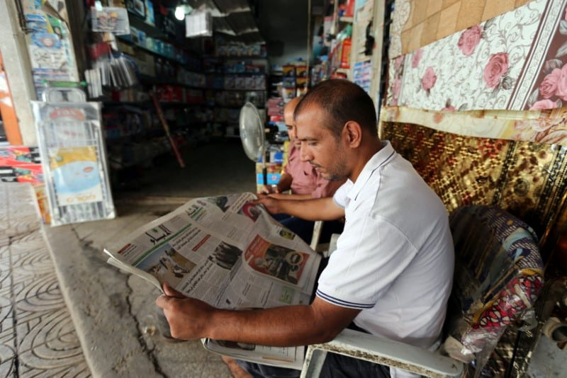 A Palestinian man reads a newspaper outside his store in Gaza City September 19, 2016. REUTERS/Ibraheem Abu Mustafa
