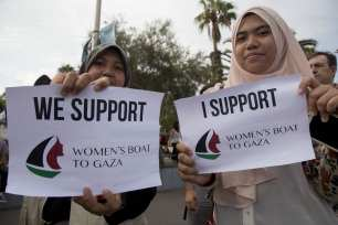 """BARCELONA, SPAIN - SEPTEMBER 14: Women show their support for two sailing boats, Amal-Hope and Zaytouna-Oliva, with only female activists on board, before it sets off for the Gaza Strip from the port of Barcelona under the banner """"The Women's Boat to Gaza"""" to break the Israeli blockade on Gaza on September 14, 2016 in Barcelona, Spain. ( Albert Llop - Anadolu Agency )"""