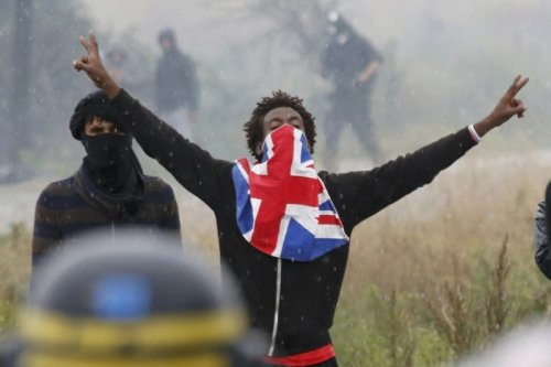 """A migrant reacts near French riot police during a protest near the area called the """"jungle"""" where they live in Calais, France, on 1 October 2016. [REUTERS/Pascal Rossigno]"""