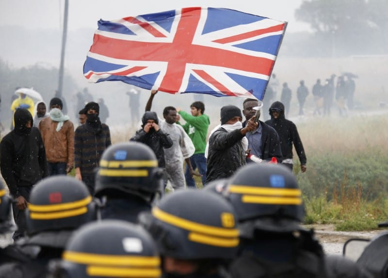 """Tear gas fills the air as French police face off with demonstrators in the camp """"jungle"""" where migrants live in Calais, France, October 1, 2016. [Reuters/Pascal Rossignol]"""