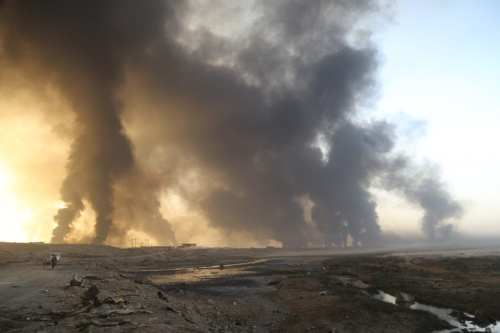Iraqi army forces arrive in Hut village as smoke rises from oil wells, set on fire by Daesh to limit coalition forces pilots' line-of-sight, near Mosul in Iraq on October 18, 2016 [Feriq Fereç / Anadolu Agency]