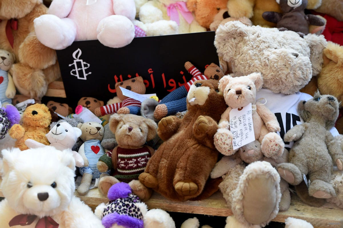 In a protest organised by War Child, Avaaz and Amnesty International in London, protestors gather with teddy bears and placards calling on the British government to take action to protect the children of the Syrian city of Aleppo outside on October 22, 2016 [Kate Green/Anadolu]