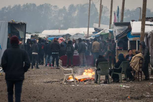 Refugees and migrants gather around fires inside the Calais 'jungle' camp in France on October 24, 2016 [Claire Thomas/Anadolu Agency]