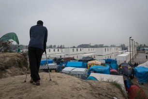 A refugee on crutches stands on a hill overlooking the containers and tents in the 'jungle' camp in Calais, France on October 24, 2016. ( Claire Thomas - Anadolu Agency)