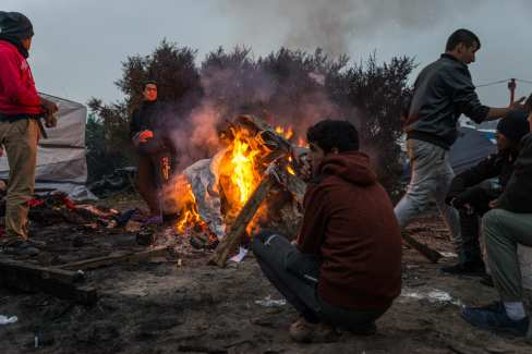 """People warm themselves with a fire in the makeshift camp known as """"the jungle"""" near Calais, France on October 24, 2016. [Claire Thomas - Anadolu Agency]"""