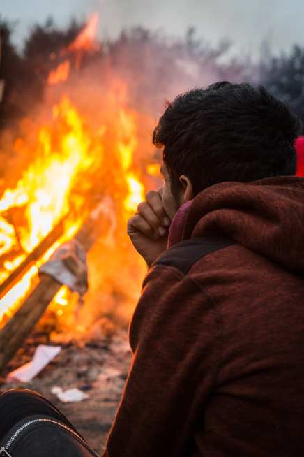A refugee from Afghanistan sits in front of a fire in the 'jungle' camp in Calais, France on October 24, 2016. ( Claire Thomas - Anadolu Agency )