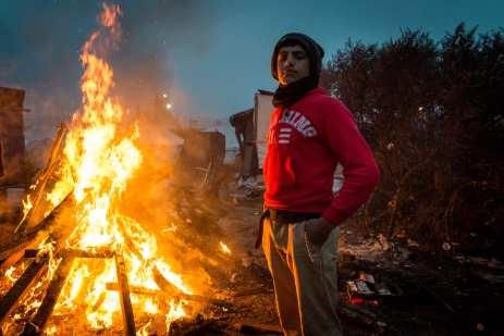 Refugees stand around a fire in the 'jungle' camp in Calais, France on October 24, 2016. ( Claire Thomas - Anadolu Agency )