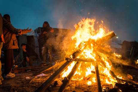 "People warm themselves with a fire in the makeshift camp known as ""the jungle"" near Calais, France on October 24, 2016. ( Claire Thomas - Anadolu Agency )"