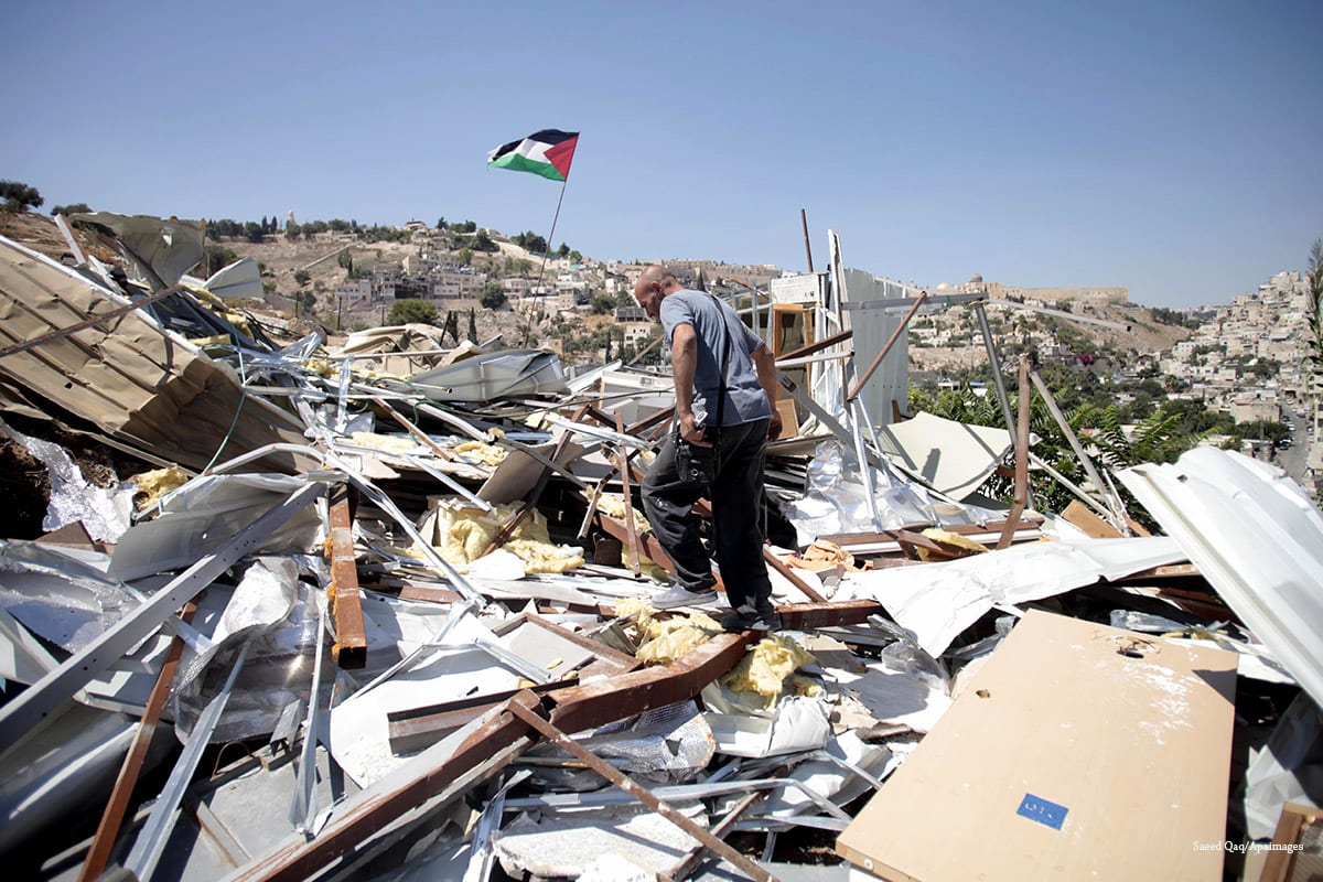A Palestinian man searches through the rubble of his home in Silwan, East Jerusalem, after Israeli forces demolished it, on 26 August, 2013 [Saeed Qaq/Apaimages]